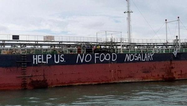 """""""Xin hãy giúp chúng tôi. Không thực phẩm. Không lương"""" - dòng chữ cầu cứu của các thủy thủ trên tàu Việt Tín 01 tại khu neo đậu Johor, Malaysia. (Ảnh: NUSPM)."""