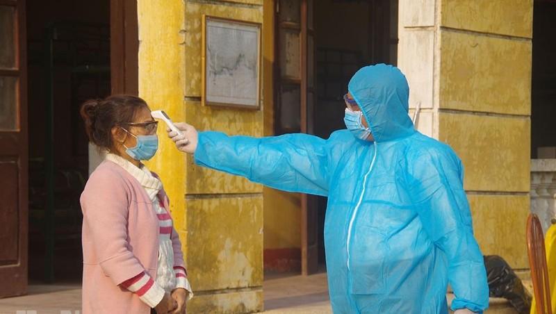 Kiểm tra thân nhiệt cho công dân trong khu cách ly theo dõi chống dịch Covid -19.