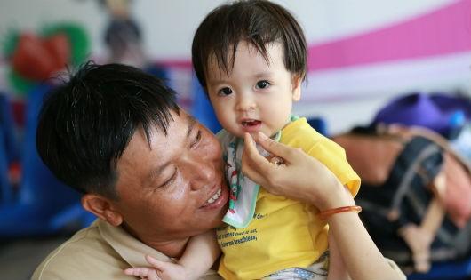 Bé Hồ Thị Minh Châu trong vòng tay người thân