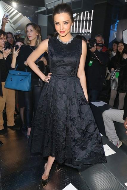 Miranda Kerr (mặc H&M) với đầm đen sang trọng nơi hàng ghế đầu của H&M.