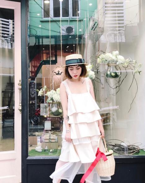 Cô chủ shop điệu đà của cửa hàng thời trang REN biết rõ bản thân hợp nhất trong những chiếc đầm xòe dịu dàng. Chiếc đầm trắng xếp tầng đi với túi cói thắt dây lụa đỏ chính là điểm nhấn cho sự ngọt ngào của cô.