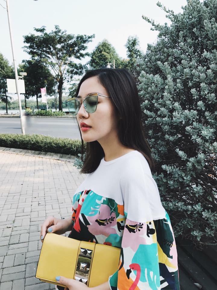 """Lại một cô nàng nữa cho thấy kính mắt màu vẫn chưa ngừng hot. Chiếc clutch vàng tỏ ra cực kỳ """"hợp rơ"""" với chiếc váy họa tiết cỏ cây mùa xuân của Văn Mai Hương."""