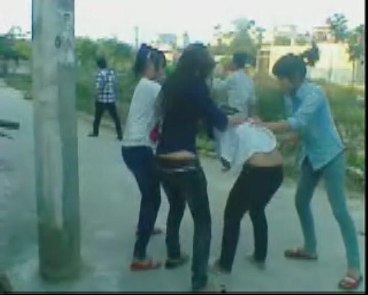Em B. bị 3 đối tượng đánh hội đồng, xé quần áo làm nhục ngay canh cổng trường của Trung tâm giáo dục thường xuyên. (ảnh cắt từ clip).