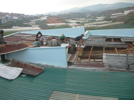 Nhà ông Lành bị tốc mái do lốc xoáy đang được bà con lối xóm hỗ trợ lợp lại