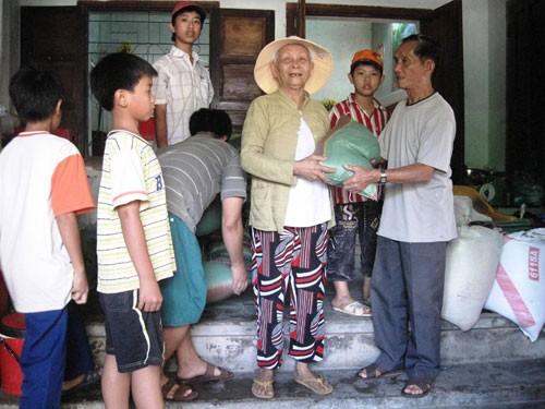 Ông NguyễnThìn (bên phải) san sẻ lộc trời bằng việc mua gạo về giúp cho những hộ nghèo đón tết