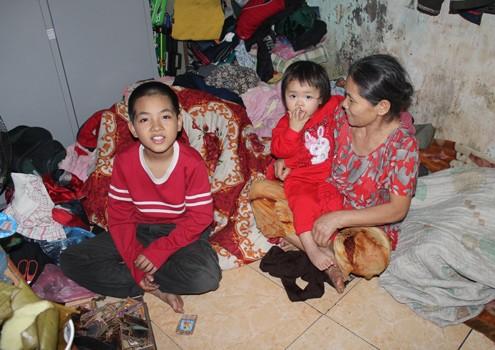 Bà Tính cùng hai đứa cháu trong căn nhà chưa có Tết. Ảnh: Bình Minh.