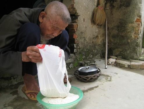 Cụ Chanh chuẩn bị gạo để gói bánh. Ảnh: Lê Hoàng.