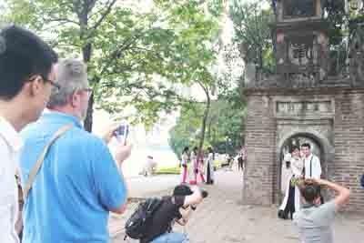 """Đứng giữa """"trái tim Hà Nội"""" tháp không chỉ thu hút các bạn trẻ, các cặp đôi đến đây chụp ảnh vào dịp cuối tuần mà còn hấp dẫn rất đông du khách. Nhưng không hiểu, sau khi ấn tượng bởi vẻ đẹp mộc mạc của tháp thì du khách quốc tế sẽ nghĩ gì với những dòng chữ vô duyên này?"""