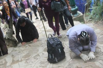 Hơn 20 người cùng thành tâm bước ba bước rồi quỳ xuống vái đi từ chân núi Yên Tử lên chùa Đồng.