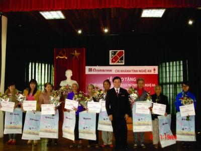 Ông Phan Hoàng Vượng - Giám đốc Agribank Nghệ An - trao sổ tiết kiệm tình nghĩa cho nữ cựu thanh niên xung phong có hoàn cảnh đặc biệt khó khăn