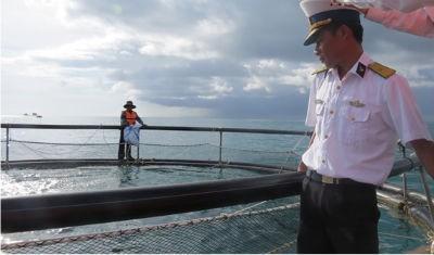 """Đội trưởng Đội nuôi cá lồng bè hải sản Trường Sa Đậu Bá Quý đang giới thiệu về """"ao"""" nuôi cá giữa Biển Đông"""