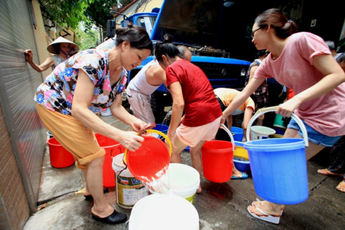 Người dân chia nhau từng xô nước từ xe bồn. Ảnh: MH