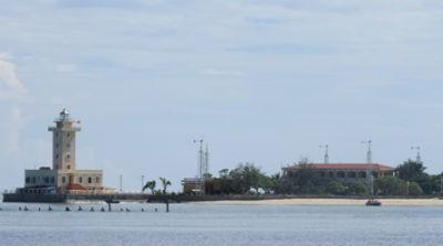 Hải đăng Sinh Tồn có kết cấu hình trụ vuông mầu vàng vững chãi nổi bật trên thảm xanh của đảo